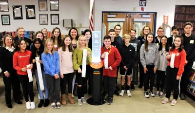 Members of the Glen Ellyn Library Foundation Board, library staff and Glen Crest students stand around the Short Story Kiosk.