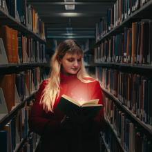 Woman standing in library stacks with a lit-up book.